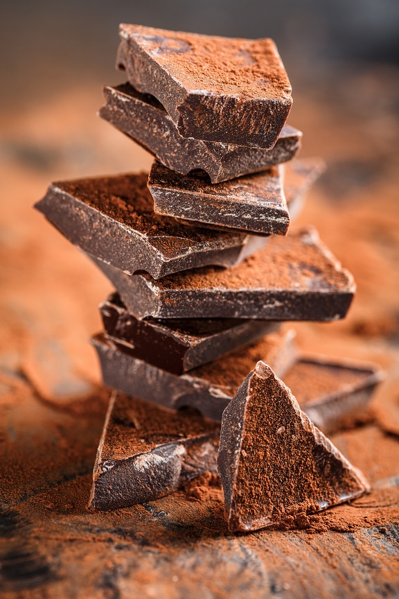 stack of dark chocolate pieces and cocoa powder